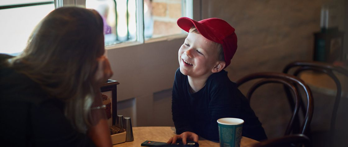 A child in a red cap enjoys a beverage with his mother at a table in the Dome Cafe in the Premier Mill Hotel