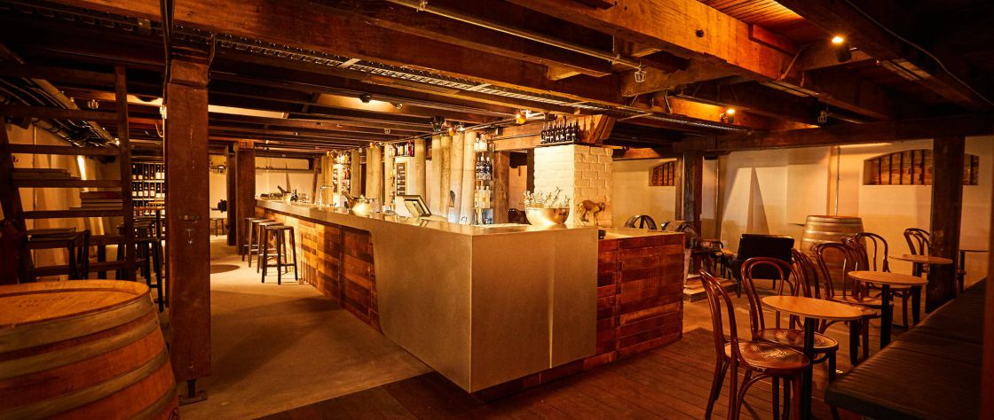 A wide shot of the Cordial Bar in the Premier Mill Hotel showing stools, wine barrels, open beams, tables and chairs