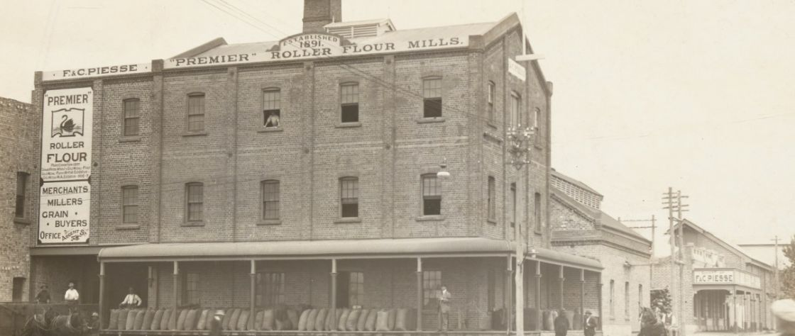 Image of the Premier Flour Mill circa 1912. Bags fille dwith grain line the verandah ready for collection.